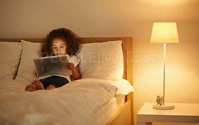 Buy stock photo A cute little girl lying in a double bed and playing on a tablet