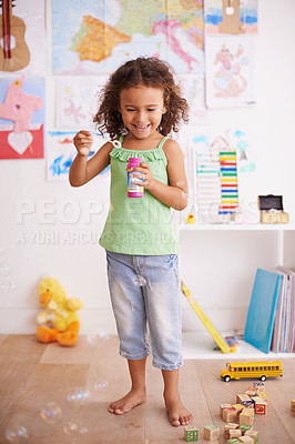 Buy stock photo Shot of an adorable little girl blowing bubbles in her bedroom