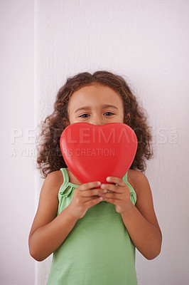 Buy stock photo Shot of a young girl smiling as she holds a heart shaped toy