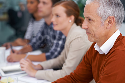 Buy stock photo Cropped shot of a handsome mature businessman sitting amongst his coworkers