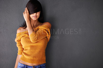 Buy stock photo Shot of an attractive young woman covering her eyes with her hair
