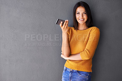 Buy stock photo Portrait of an attractive young woman standing with a mobile phone against a gray wall