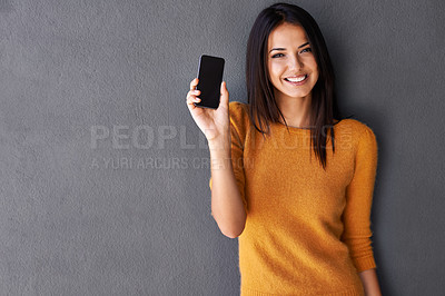 Buy stock photo Portrait of an attractive young woman holding up a mobile phone