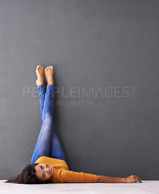 Buy stock photo Shot of a young woman lying on the floor with her feet against the wall
