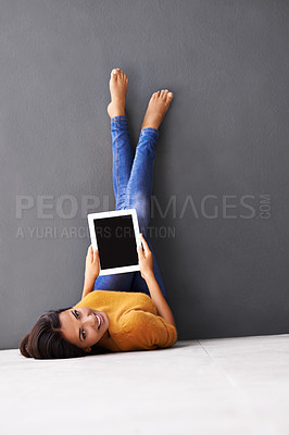 Buy stock photo A young woman holding a digital tablet while lying on the floor with her feet against the wall