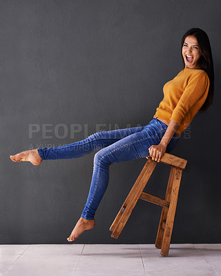 Buy stock photo Portrait of an excited young woman leaning back on a stool