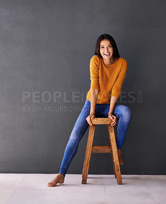 Buy stock photo Portrait of a happy young woman sitting on a stool against a gray wall
