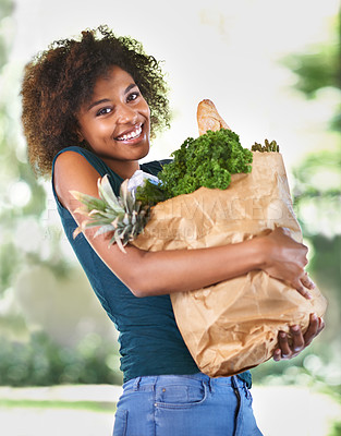 Buy stock photo Cropped shot of an attractive young woman carrying a grocery bag