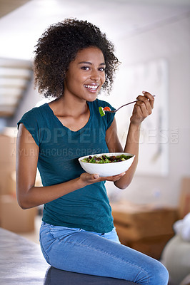 Buy stock photo A beautiful young woman eating a bowl of salad at home