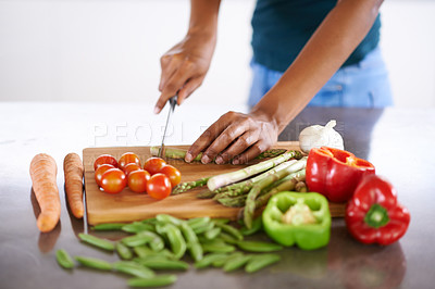 Buy stock photo Cropped closeup shot of a woman cutting up vegetables on a cutting board