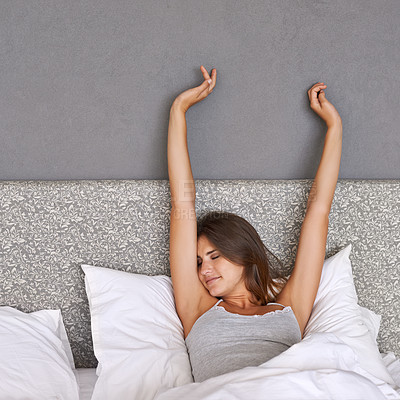 Buy stock photo An attractive young woman stretching in bed after waking up