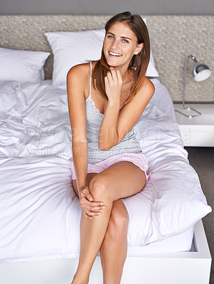 Buy stock photo Cropped shot of an attractive young woman sitting on her bed