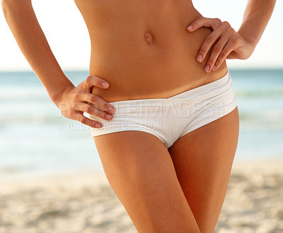 Buy stock photo Cropped shot of a young woman standing with her hands on her hips at the beach