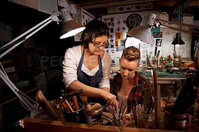 Buy stock photo Shot of two young woman working on handmade crafts together