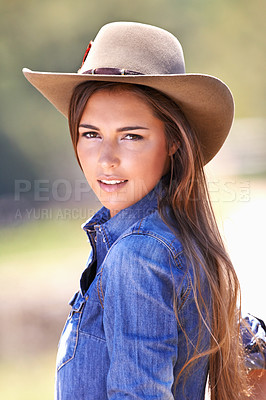 Buy stock photo Portrait of an attractive young cowgirl standing in the sun