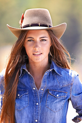 Buy stock photo An attractive young cowgirl standing in the stables