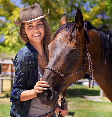 Buy stock photo Portrait of a young cowgirl standing with her horse