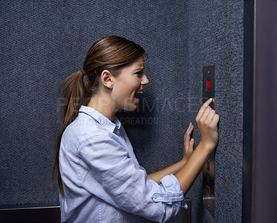 Buy stock photo Shot of a fearful woman shouting into an elevator intercom