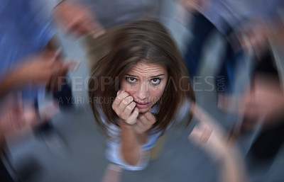 Buy stock photo Conceptual shot of an anxious young woman in the middle of a circle of accusing coworkers
