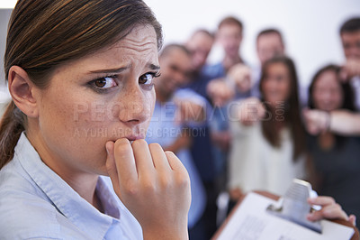 Buy stock photo Closeup of an anxious young woman facing the accusatory fingers of her coworkers