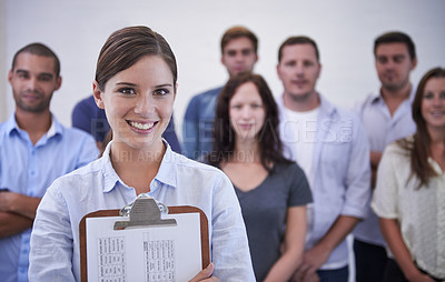 Buy stock photo Portrait of a smiling young woman standing in front of her coworkers