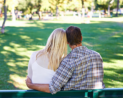 Buy stock photo Rearview of an affectionate young couple sitting on a park bench