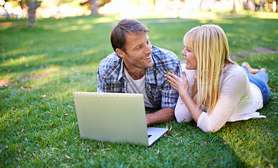 Buy stock photo Cropped shot of an attractive couple using a laptop outdoors