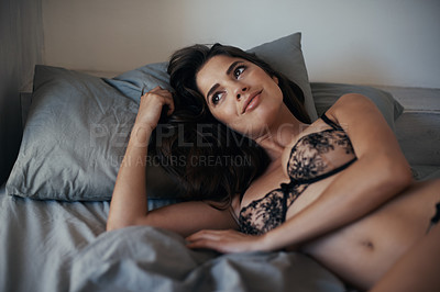 Buy stock photo Shot of a gorgeous young woman lying on the bed in her underwear