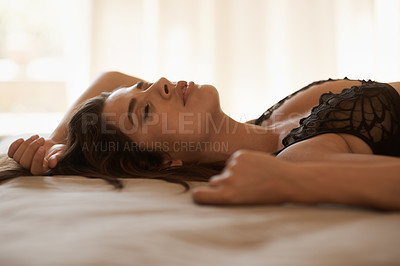 Buy stock photo Shot of a beautifully seductive young woman lying on her bed in black lingerie