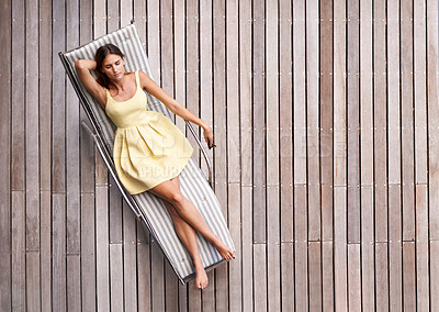 Buy stock photo A young, wealthy woman lying on her sunbed
