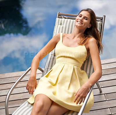 Buy stock photo A pretty young lady relaxing on a deck chair at the sea shore