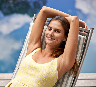 Buy stock photo A beautiful woman relaxing on a deck chair next to the pool while on holiday