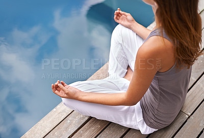 Buy stock photo Cropped closeup of a young woman meditating poolside