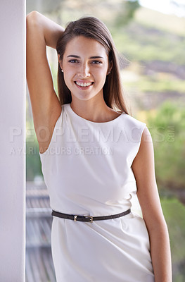 Buy stock photo Cropped shot of a young woman leaning against a wall