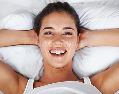 Buy stock photo A beautiful young woman smiling at the camera as she lies in bed