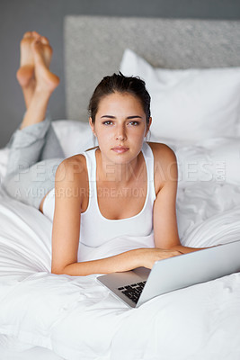 Buy stock photo Portrait of an attractive young woman using her laptop in bed