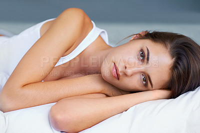 Buy stock photo A young woman looking sad while lying on her bed