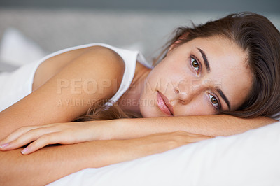 Buy stock photo A beautiful young woman looking sad while lying on her bed