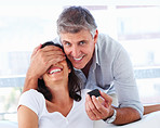 Mature man covering his wife's eyes to surprise her with a ring
