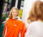 Young woman holding an orange full sleeve dhirt and looking at herself in the mirror