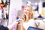 Happy young woman making her shopping payment with a credit card