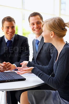 Buy stock photo Cropped shot of a group of corporate businesspeople working together on a laptop