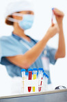 Blur image of a female lab worker holding up test tube