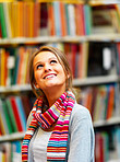 Young smiling lady looking upwards in library