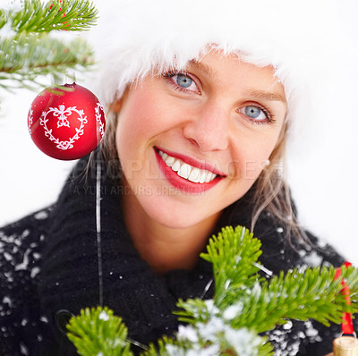 Buy stock photo Pretty woman in a winter cap alongside a Christmas tree - isolated on white