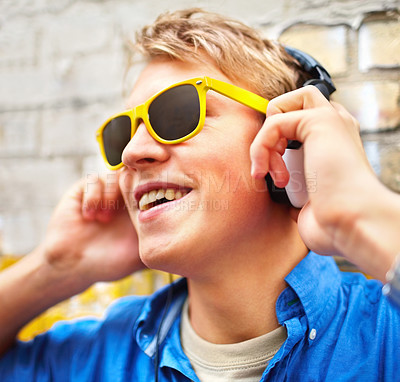 Buy stock photo Trendy young guy wearing bright yellow sunglasses listening to music on his headphones