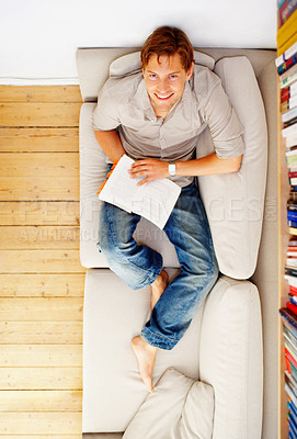 Buy stock photo Young man relaxing with a book.