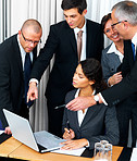 Group of happy business men and women looking at laptop