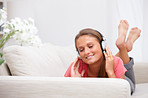 Closeup of a girl lying on sofa and listening to music