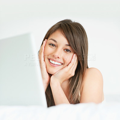 Buy stock photo Smiling young lady lying with a laptop